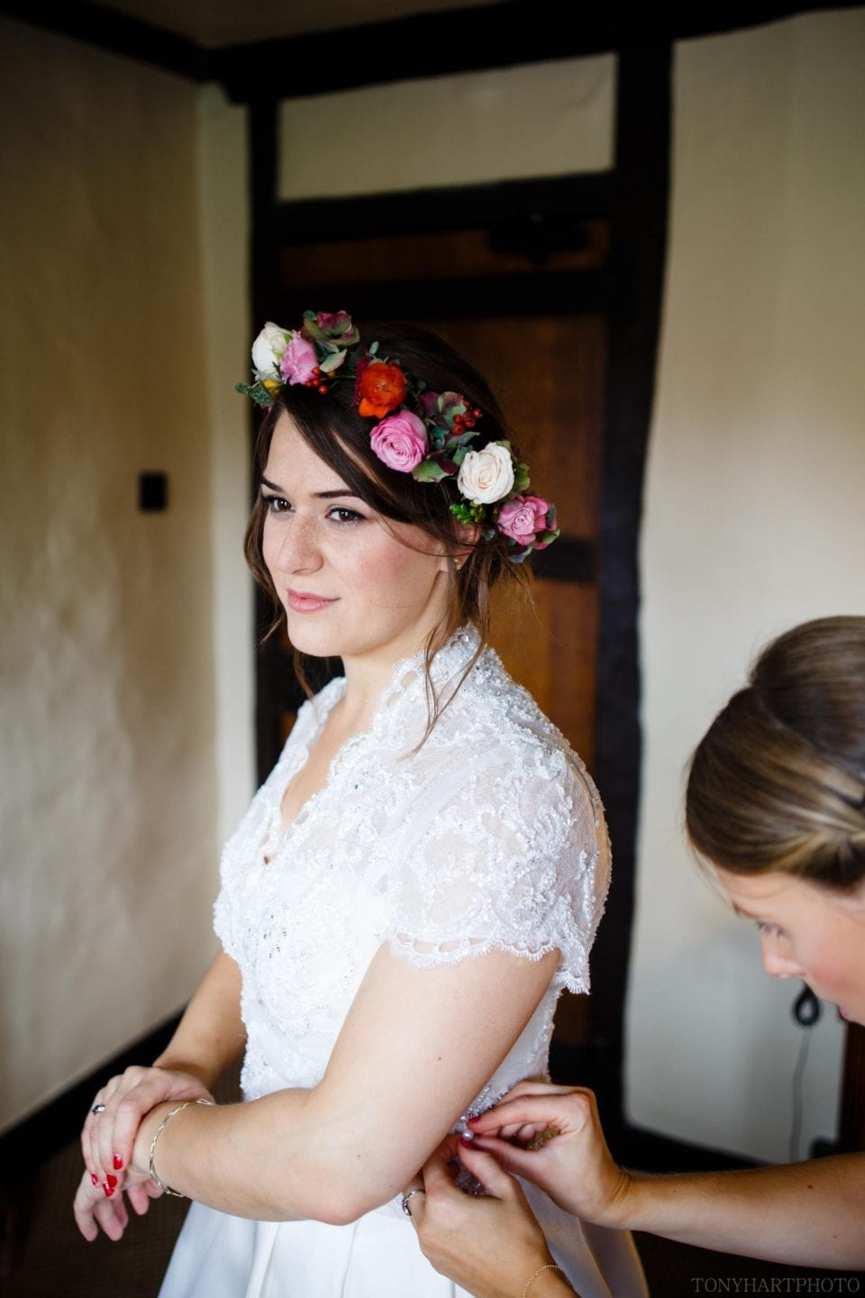 Ali wearing her beautiful flower crown as her bridesmaids make the final adjustments to her dress