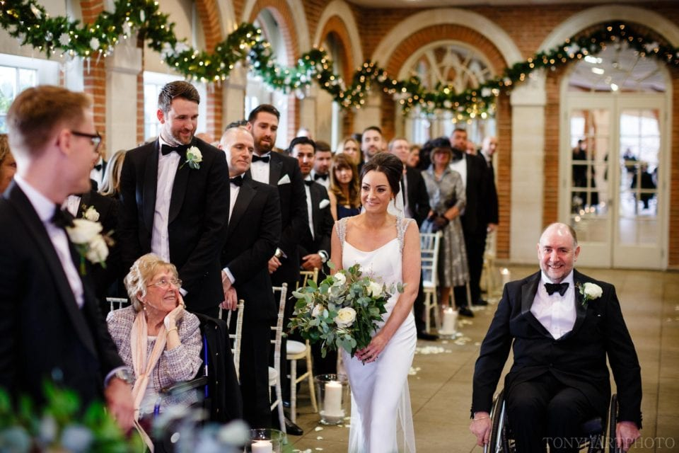 Christie and her Dad coming up the aisle in the Orangery at Great Fosters