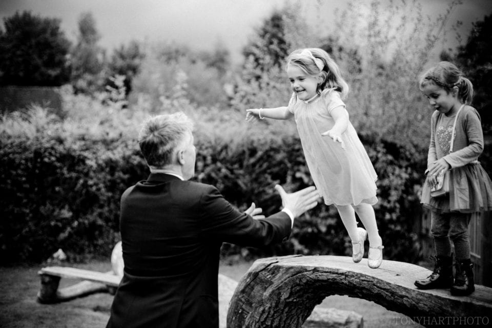 A young wedding guest taking a leap of faith at The Bluebell Pub, Dockenfield
