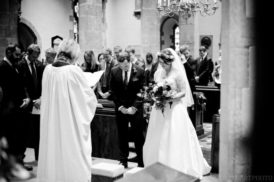 Ali & Nic at the chancel step during their wedding ceremony at Chiddingfold Church