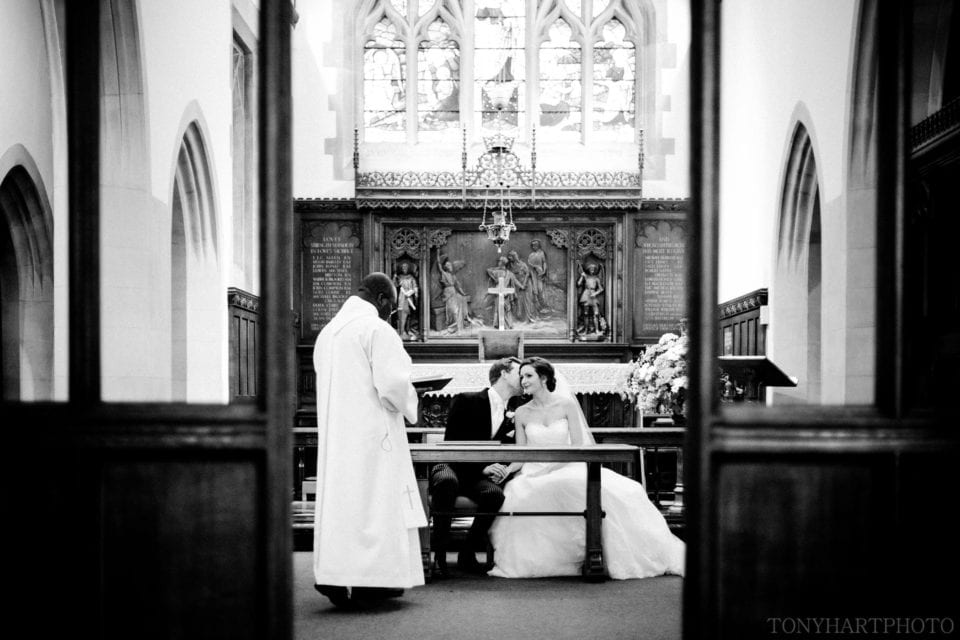 Penny & James sharing a private whisper during their wedding ceremony in Weybridge