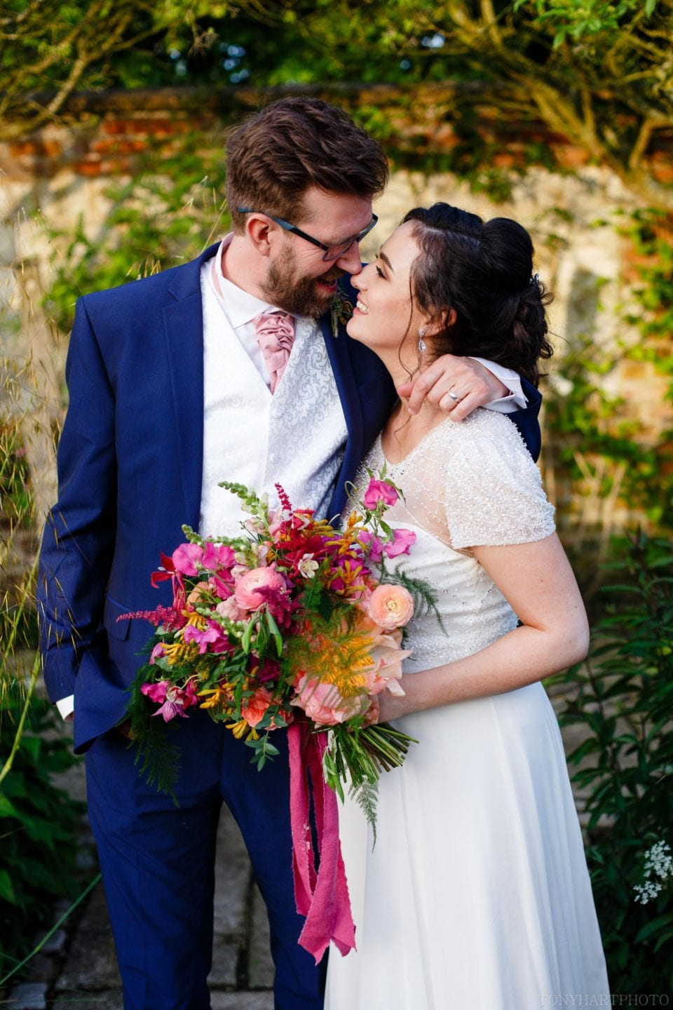 Laura & Andy enjoying the evening sunshine at Bury Court Barn. Stunning flowers by Hannah Berry Flowers.