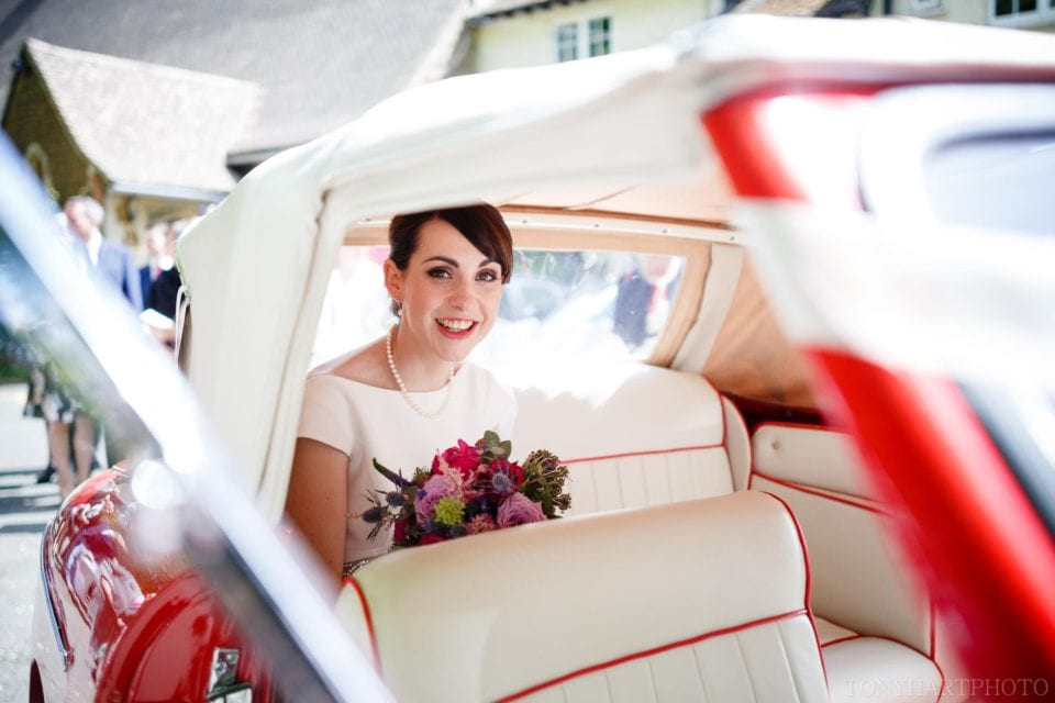 Emma in the back of her lovely red wedding car