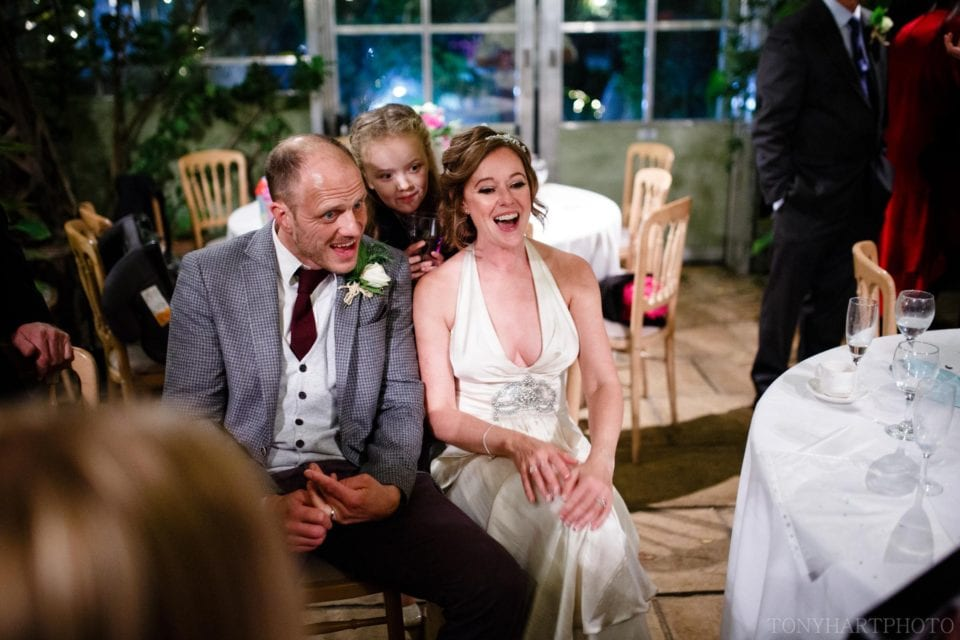Emma & Tom reacting to their caricatures during their wedding at West Green House
