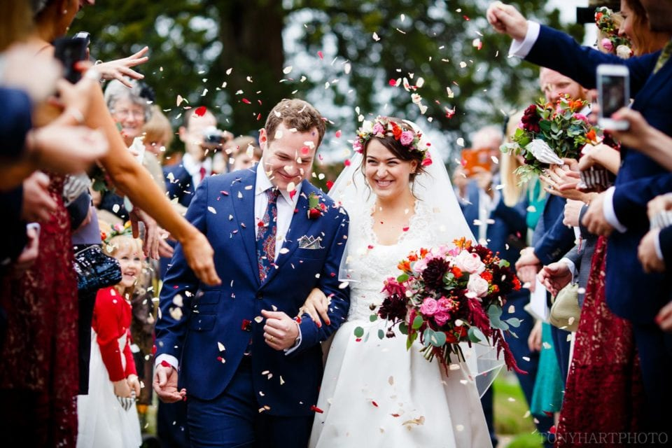Ali & Nic making their way down the path at Chiddingfold Church while being pelted with generous amounts of confetti!