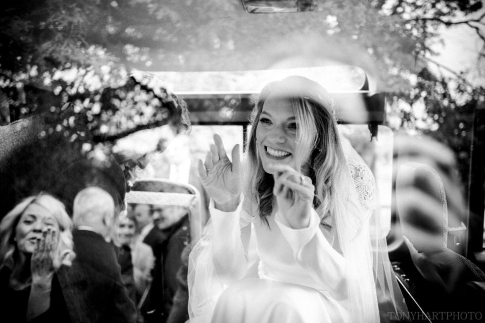 Bride Anna waves through the glass of the Land Rover