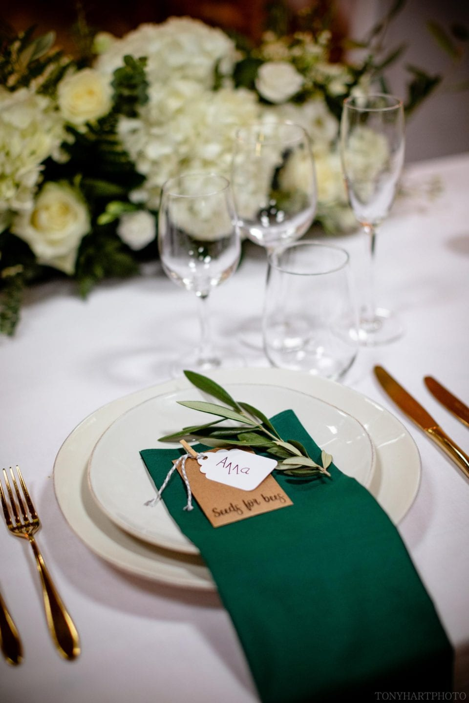 Place setting detail featuring green napkins and gold cutlery