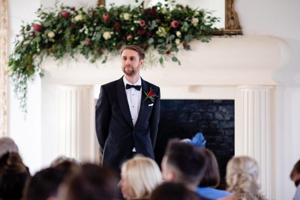 Groom James awaits his bride in The Vine Room