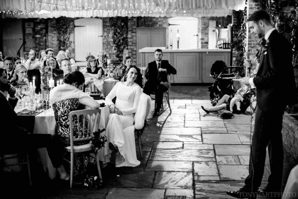Northbrook Park Wedding Photography - The Orangery during the Groom's speech. Jemima listens in.