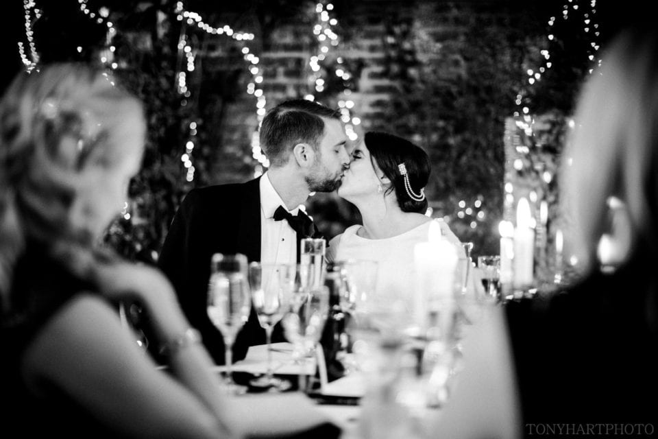 Northbrook Park Wedding Photography - Bride and Groom share a kiss following the wedding speeches