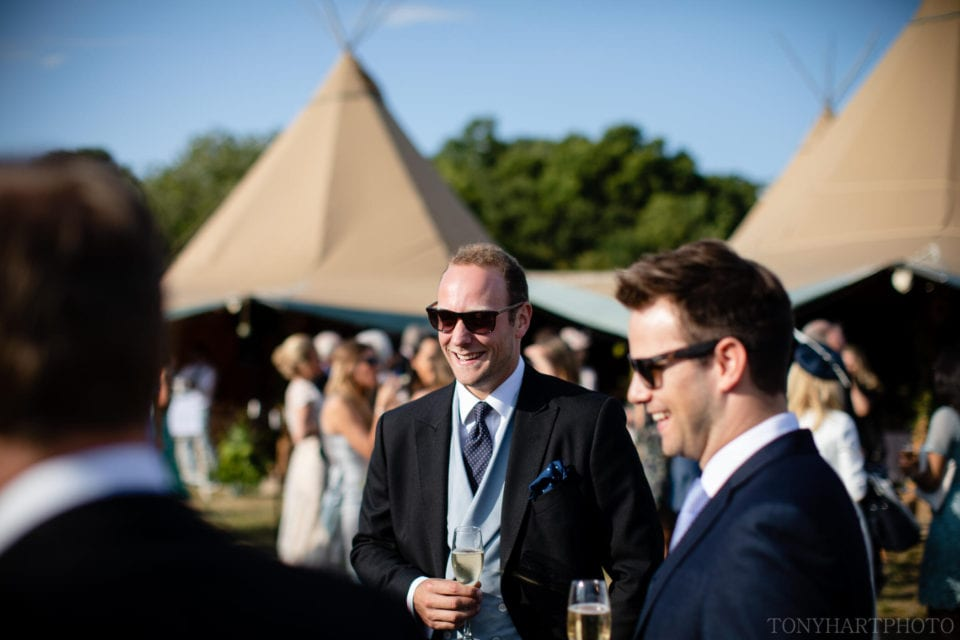 Guests enjoying the sunshine at Jumbo & Grace's Tipi wedding