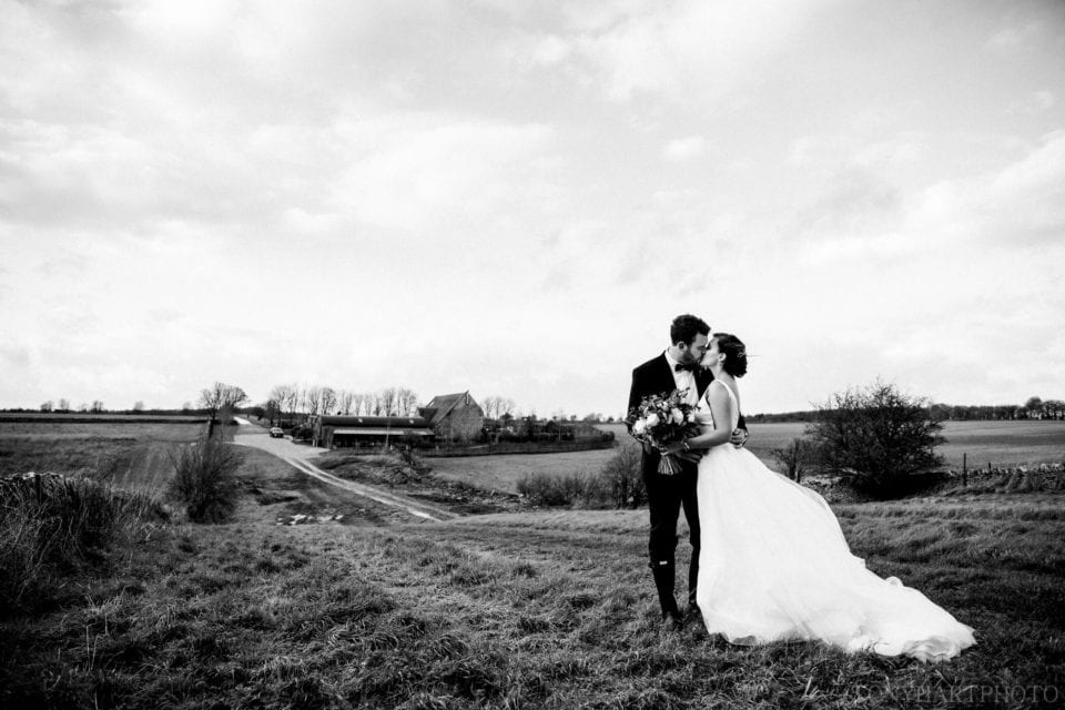 Black and white bride and groom portrait with Stone Barn in the background