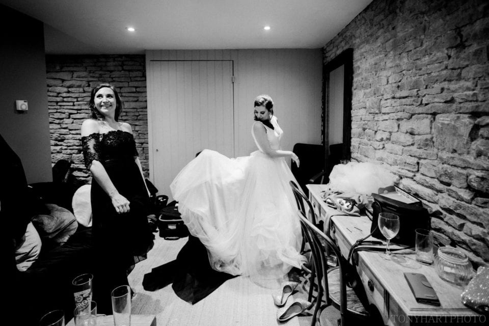 Getting the dress bussled ahead of the first dance at Stone Barn