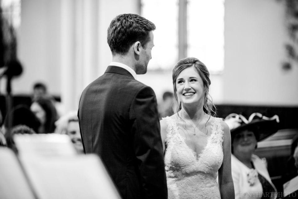 Lauren & Scott exchange a look during their wedding ceremony at Farnham URC