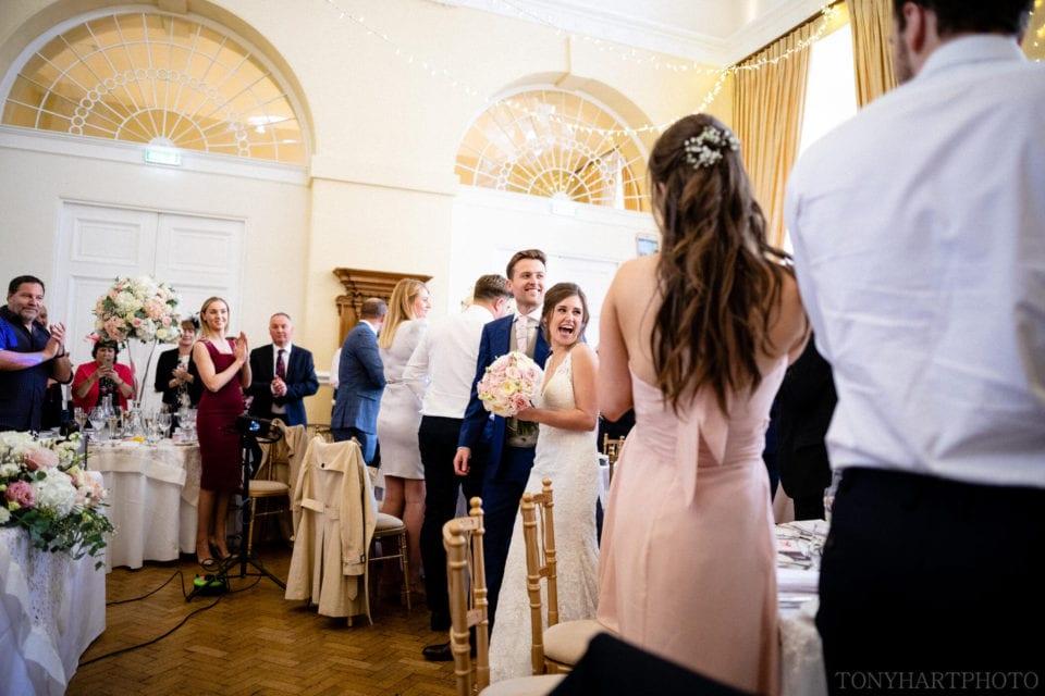 Guests welcome Lauren & Scott into their wedding breakfast art Farnham Castle