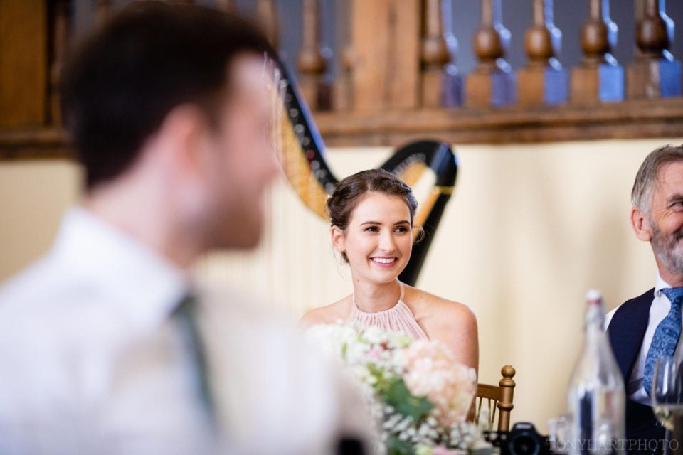 Bridesmaid listens to the speeches during the wedding breakfast at Farnham Castle