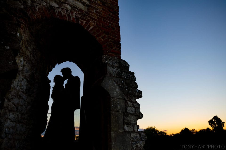 Couple silhouetted in an archway at Farnham Castle