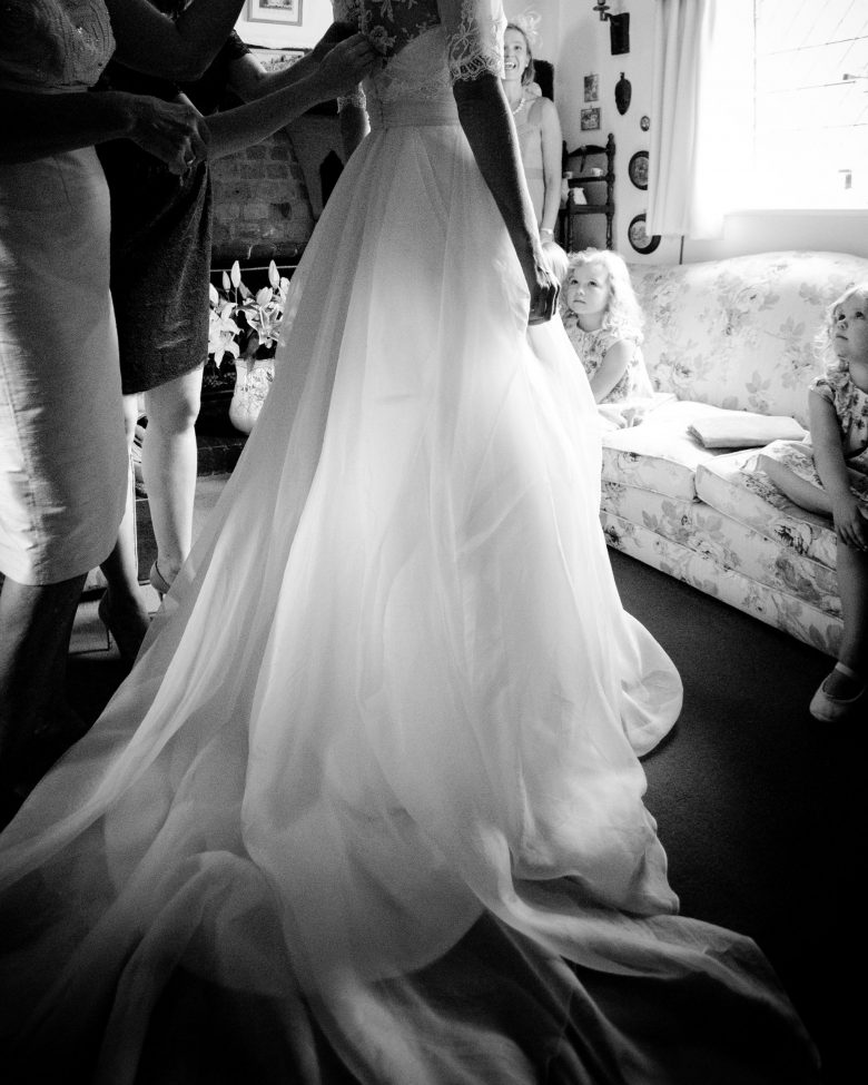 A flower girl watches on, in awe, as the bride gets into her dress.