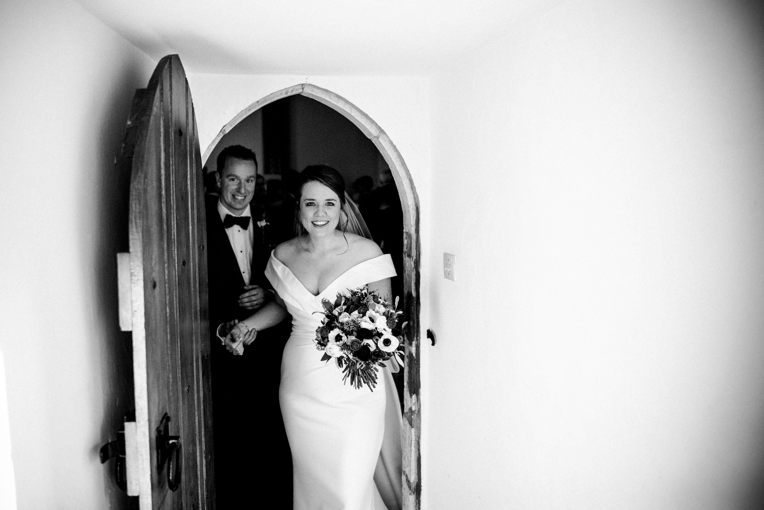 Pip & Mark walk out of their wedding ceremony in the Norman Chapel at Farnham Castle.